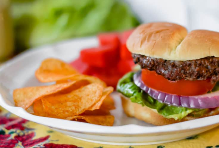 grilled hamburgers made with best grilled hamburger marinade served on a plate with chips and watermelon