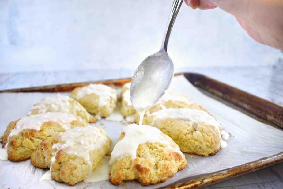 spoon drizzling glaze on scone