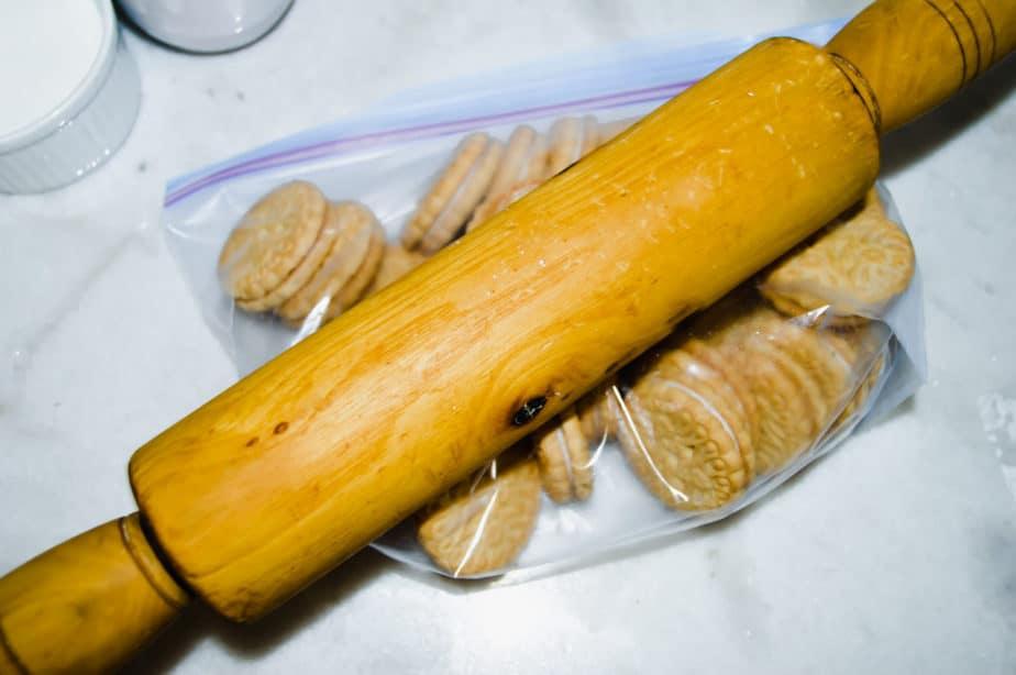 rolling pin crushing bag of vanilla cookies