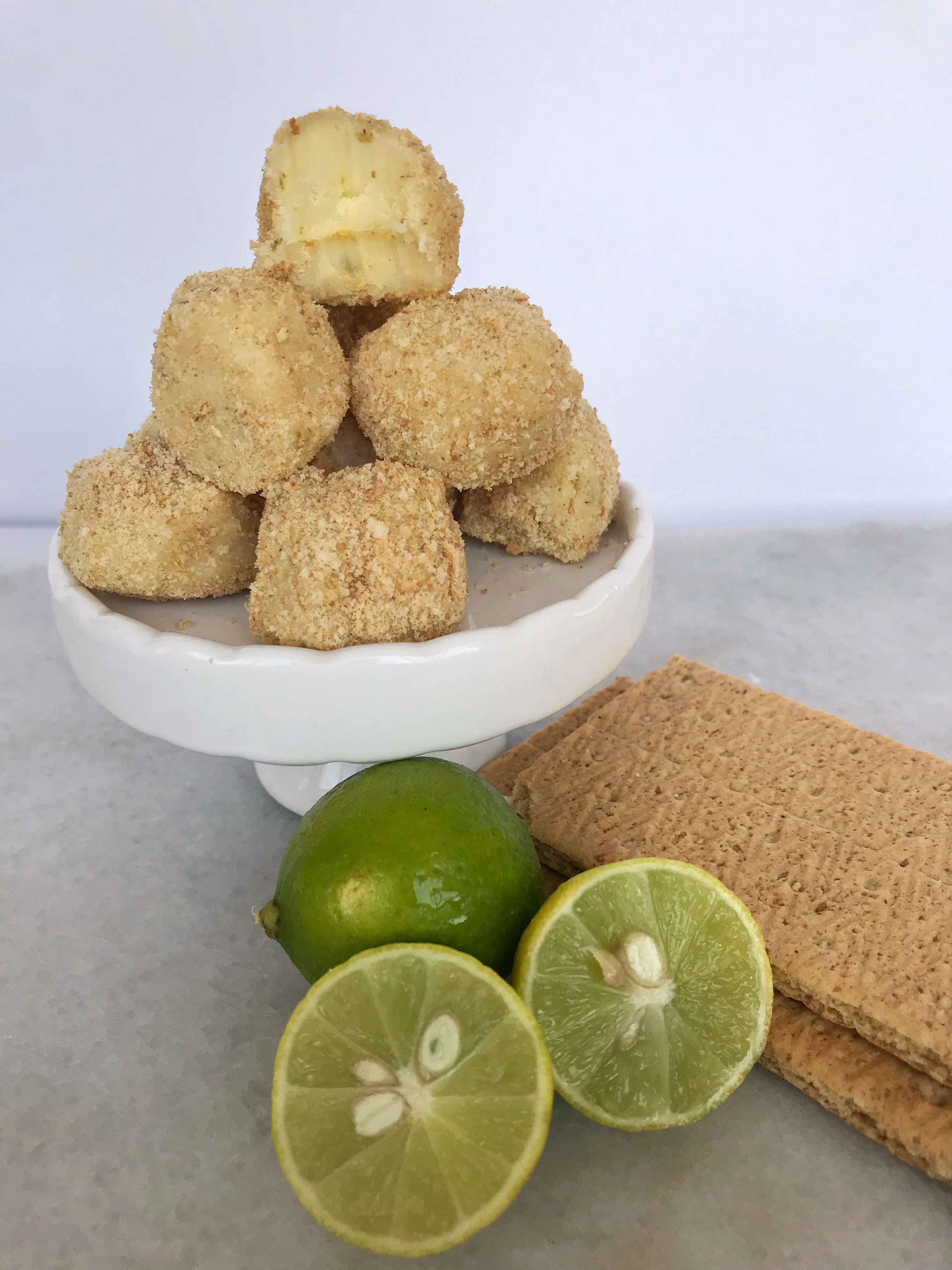 key lime pie truffles on stand with limes and graham crackers