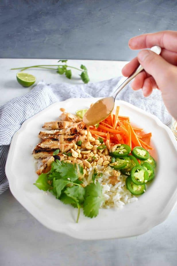 thai rice bowl with peanut sauce being drizzled over top
