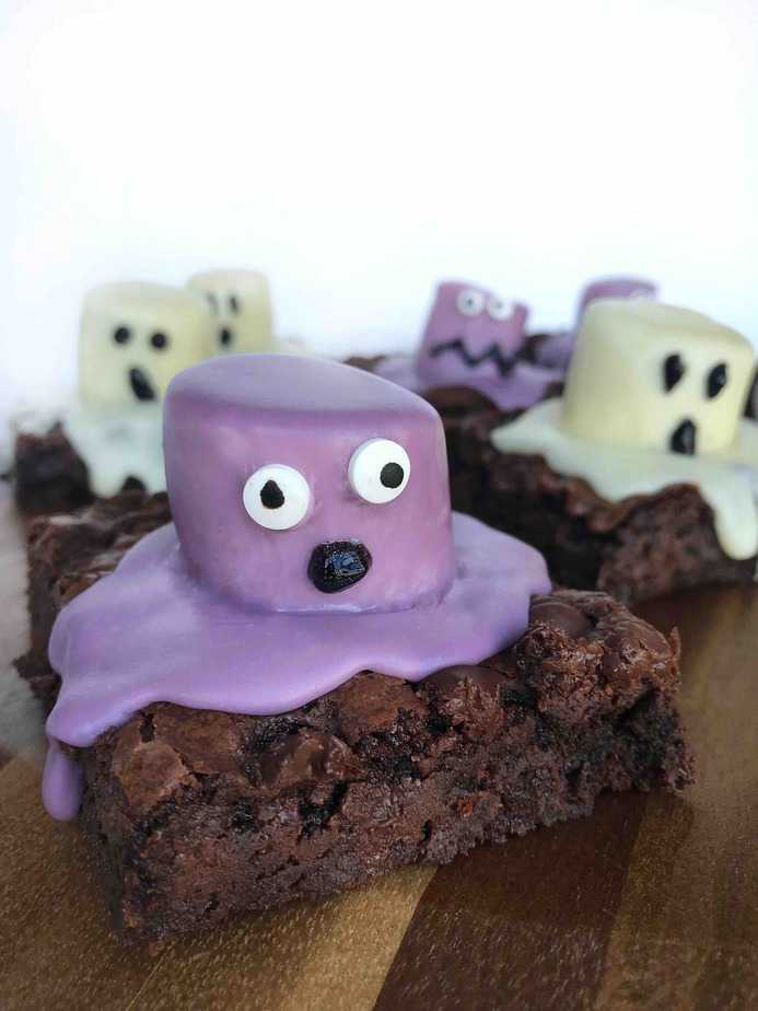 purple monster brownie with OH shaped mouth on wooden board with ghost brownies in background