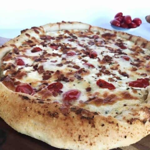 whole homemade pizza on a wooden board with paddle
