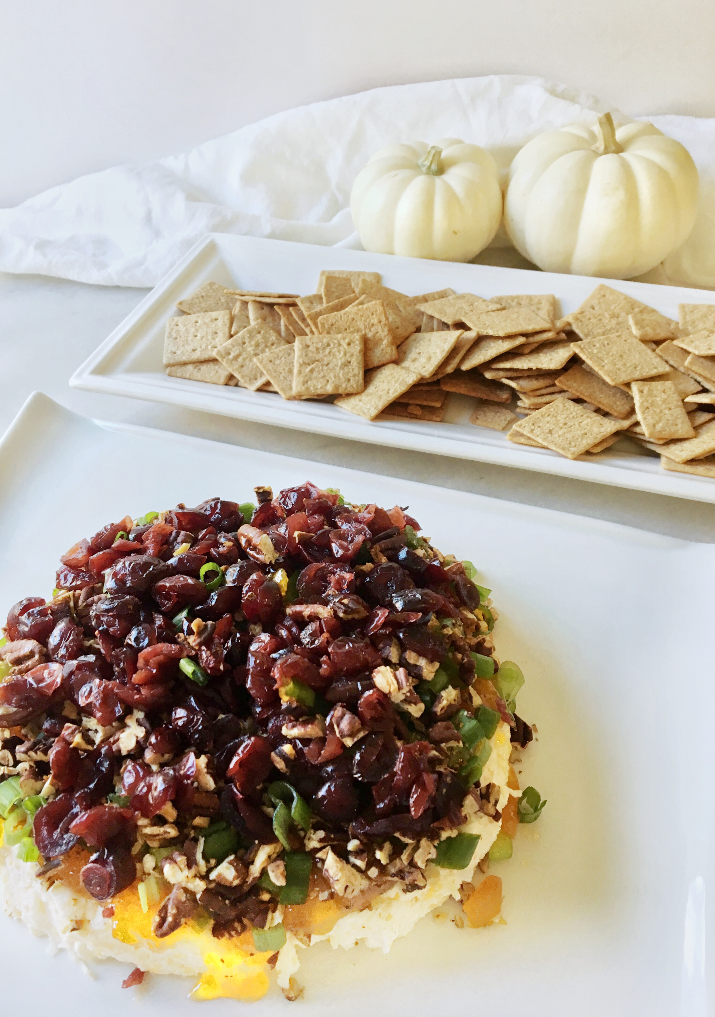 crackers with a layered cheese spread appetizer on white platters