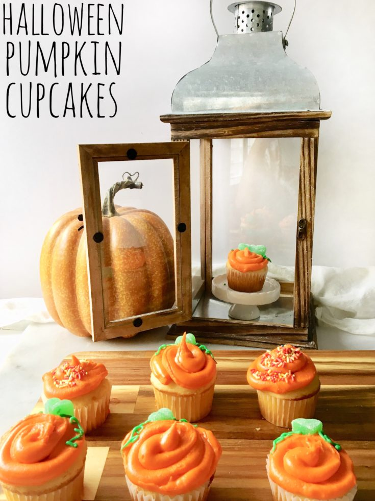 vanilla cupcakes frosted with orange buttercream to look like Halloween pumpkins