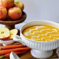 white tureen filled with carrot apple soup. stack of fresh apples and carrots