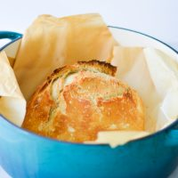 blue pot filled with round loaf of easy artisan bread