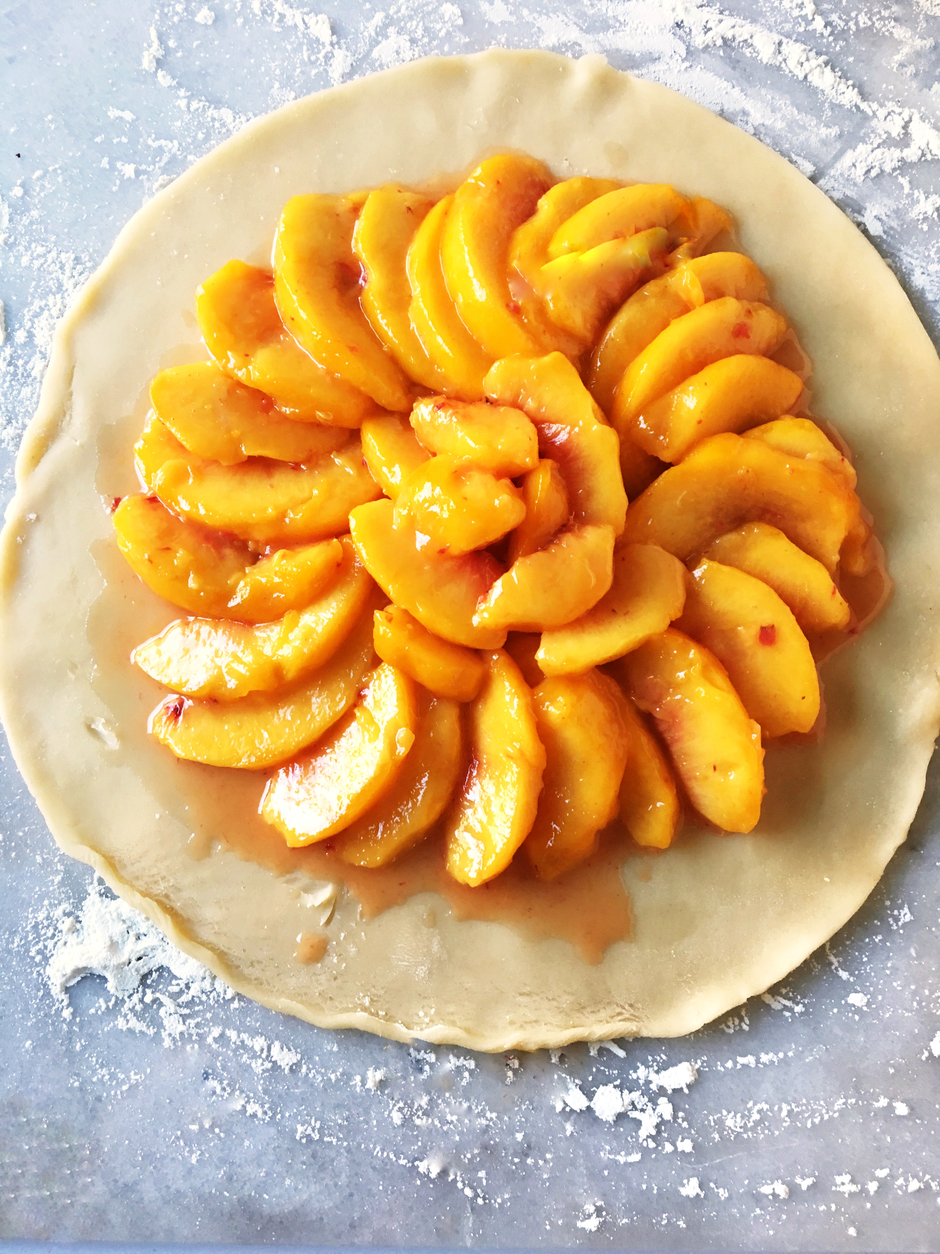 fresh peaches laid in a spiral over round pastry crust