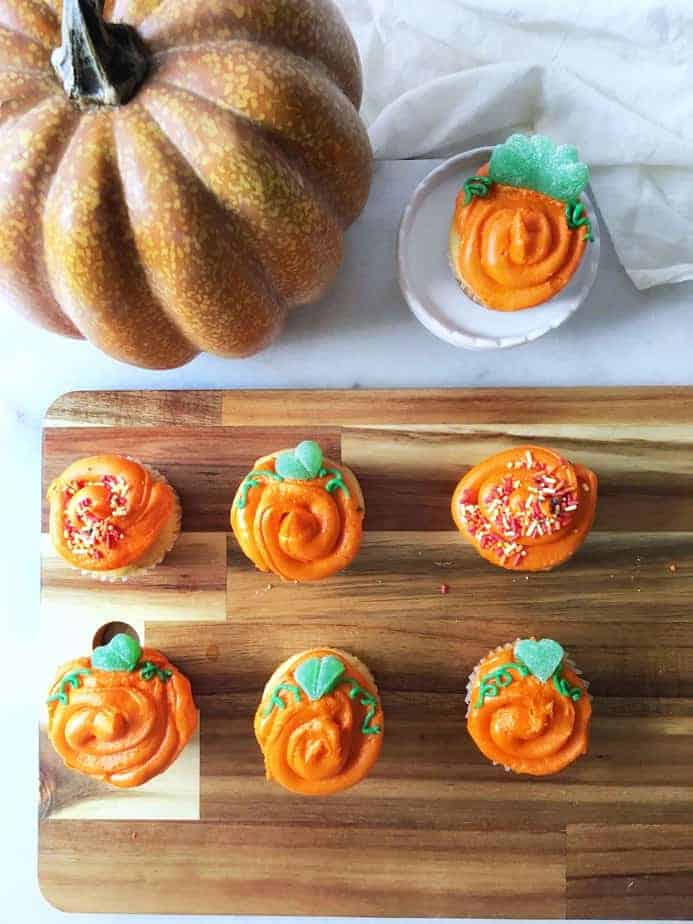 pumpkin cupcakes with an artificial pumpkin for halloween