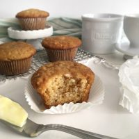 brown sugar muffins with one bite gone and butter on knife