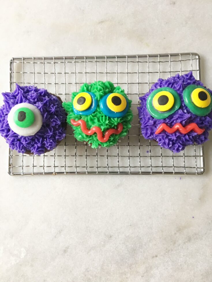 a trio of cupcakes decorated like monsters in shades of purple and green