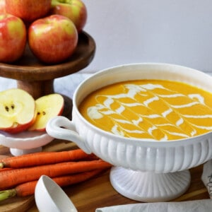 A large white bowl and ladle with carrot soup, apples and carrots.