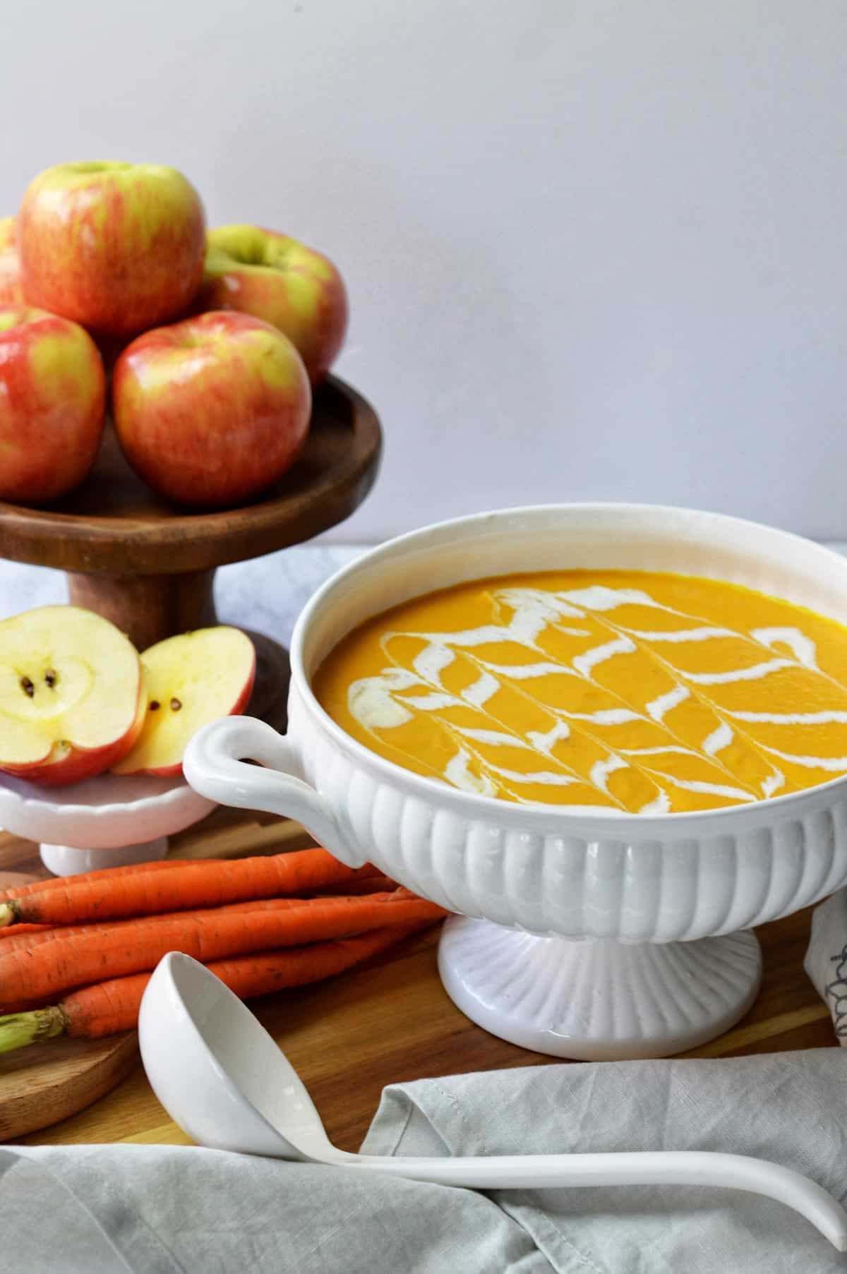 White soup tureen of carrot apple soup with bowl of apples and carrots.