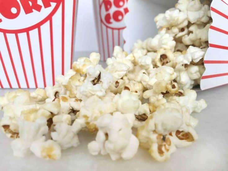 popcorn spilling out of a a red and white striped popcorn bucket