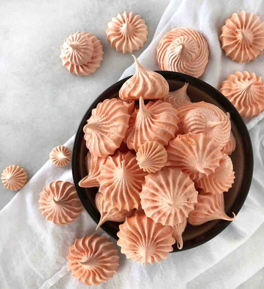 overhead shot of meringue cookies in bowl and scattered over dish cloth