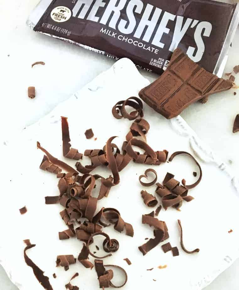 chocolate curls on a white plate with Hershey's bar