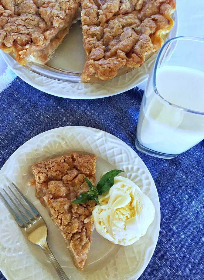 Brown Bag Apple pie on white plate with ice cream and whole pie with missing piece