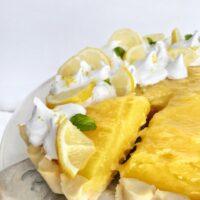 lemon meringue pie slice being removed from large pie