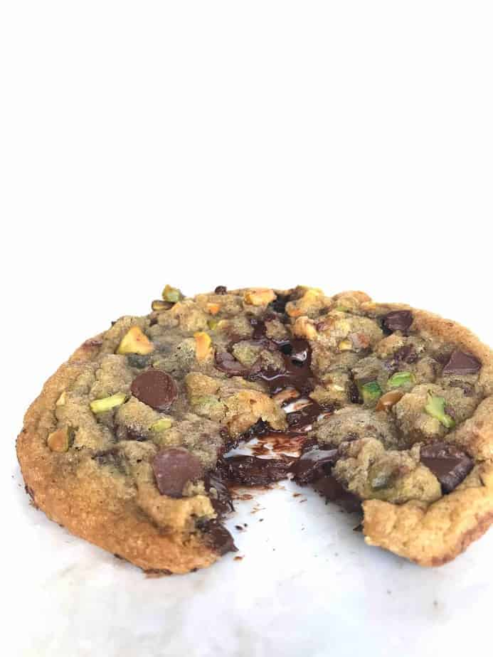 gooey melty dark chocolate pistachio tahini cookie being pulled apart