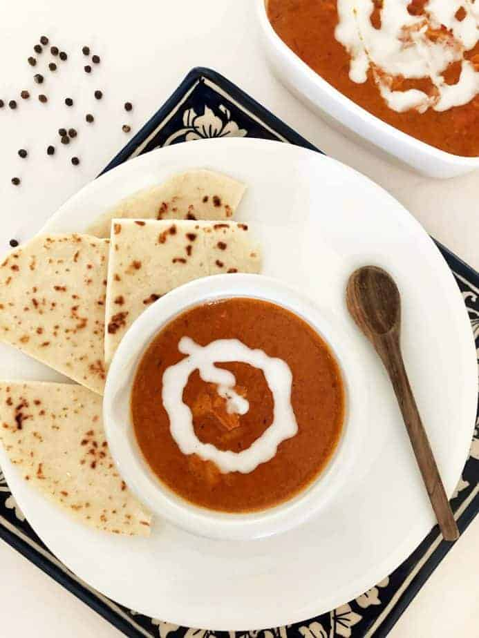 white bowl of red sauced Indian butter chicken with side of naan bread makes delicious dinner of indian food
