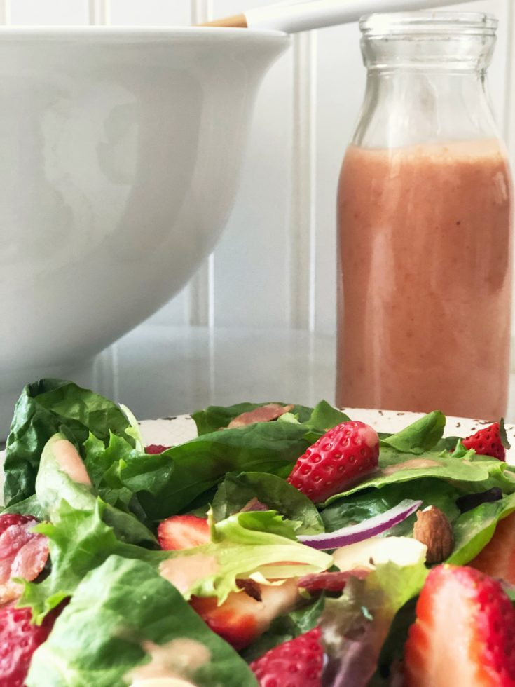 bottle of pink fresh strawberry vinaigrette and plate of strawberry spinach salad