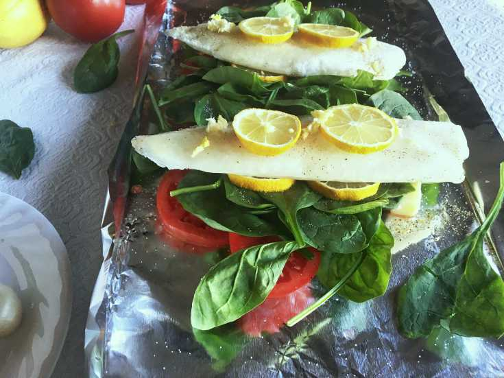 foil stacked with tomatoes, spinach, Tilapia and lemon