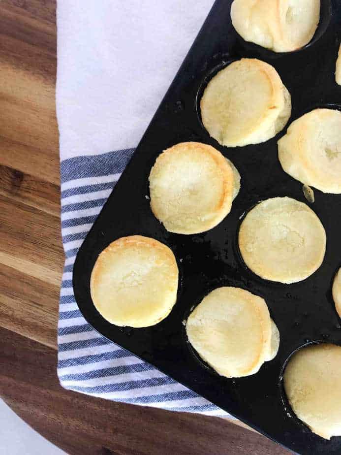 cheese breads sitting in a mini muffin tin