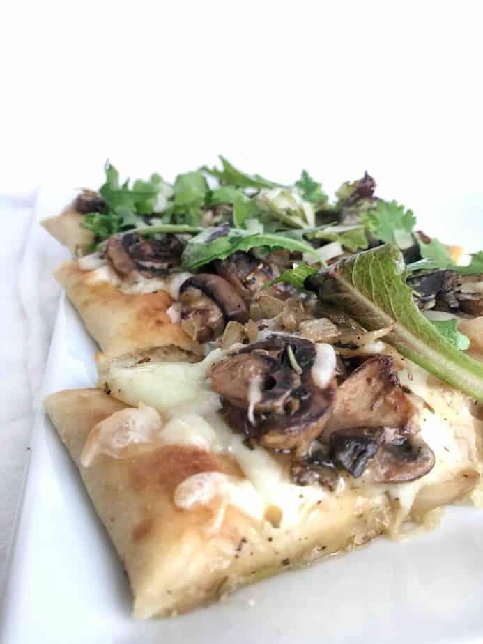 slices of mushroom flatbread on a white platter