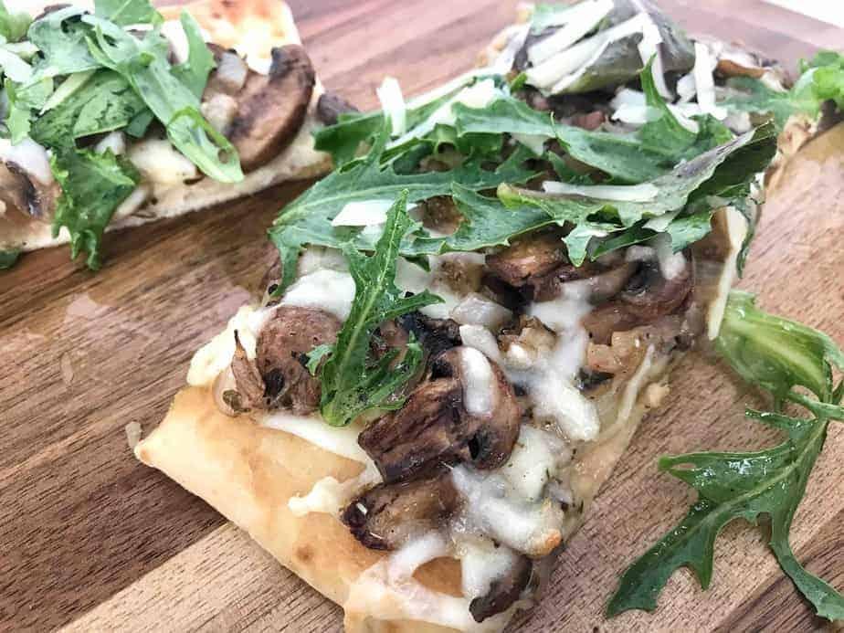 mushroom flatbread pizza with arugula on top
