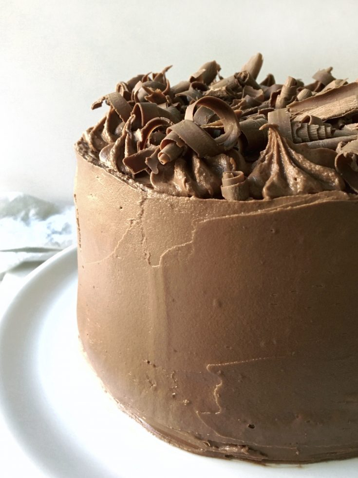 chocolate fudge frosting spread over a 3 layer cake