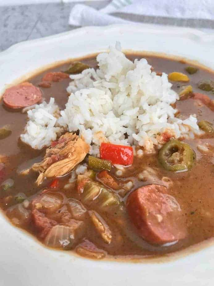 chicken and sausage creole gumbo in white bowl with rice on top
