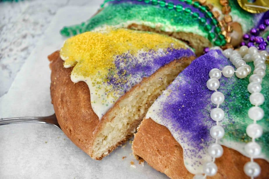 slice being removed from a king cake ring with colored sanding sugar