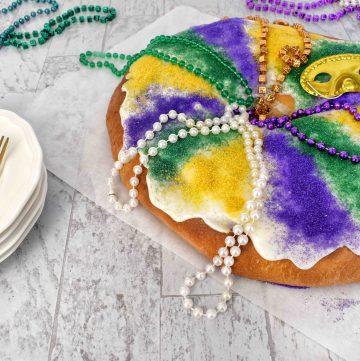 full mardi gras king cake with mardi gras beads and paltes