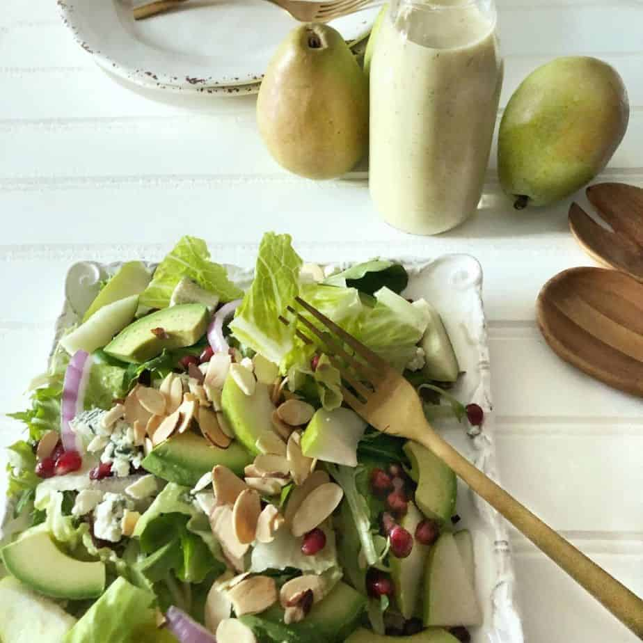 white square plate with lettuce, pears, pomegranates and bleu cheese