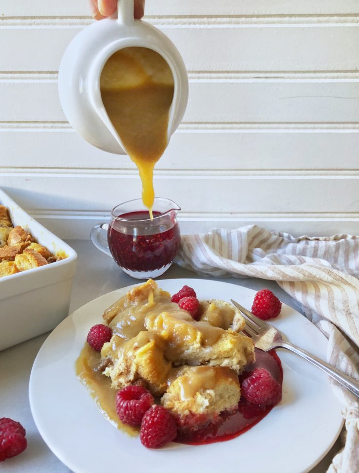 bowl full of bread pudding with raspberry and caramel sauce pouring out