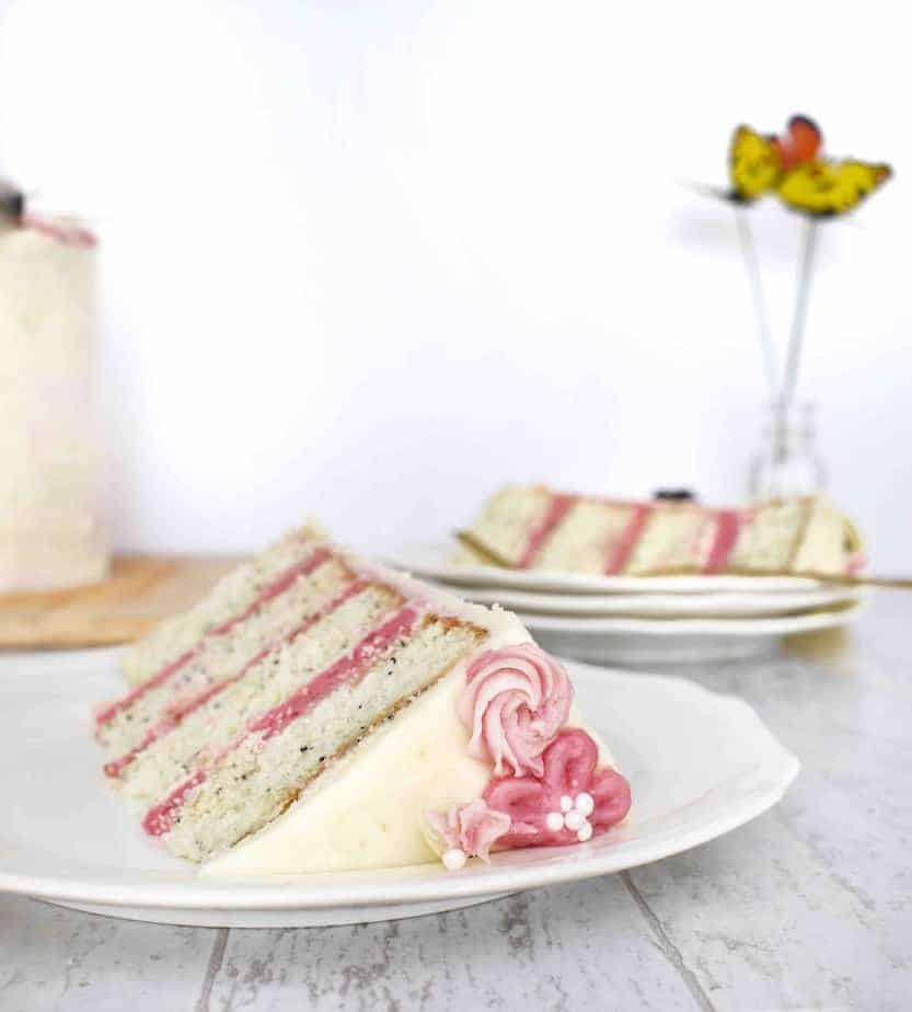 slice of blackberry lemon poppyseed cake with bright pink blackberry buttercream frosting in between and white lemon cream cheese frosting on outside