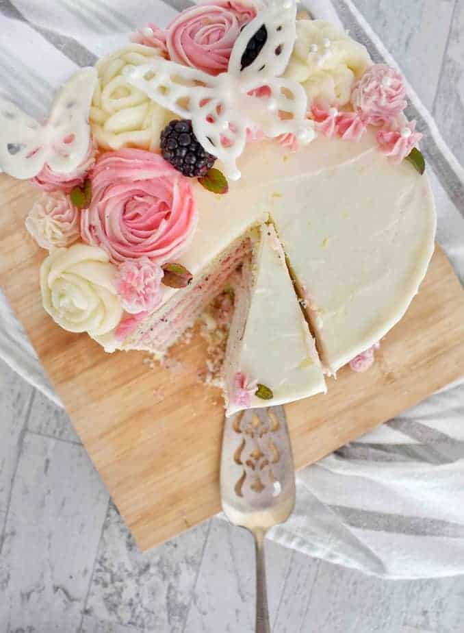 overhead shot of blackberry lemon poppyseed cake with pink and white buttercream flowers and white chocolate butterflies