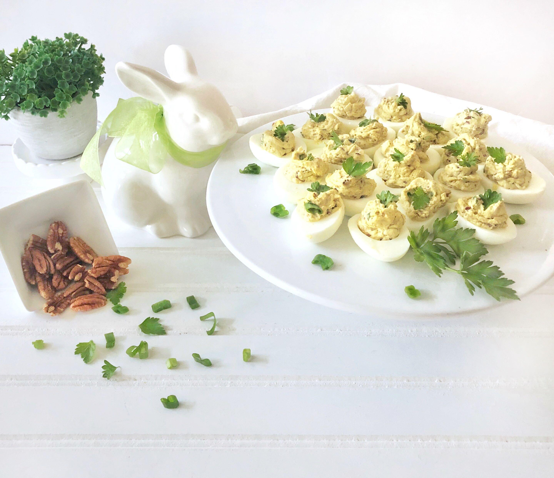 ceramic Easter bunny overlooks platter of gourmet deviled eggs