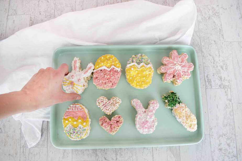 Easter rice krispie treats on blue tray with hand grabbing one