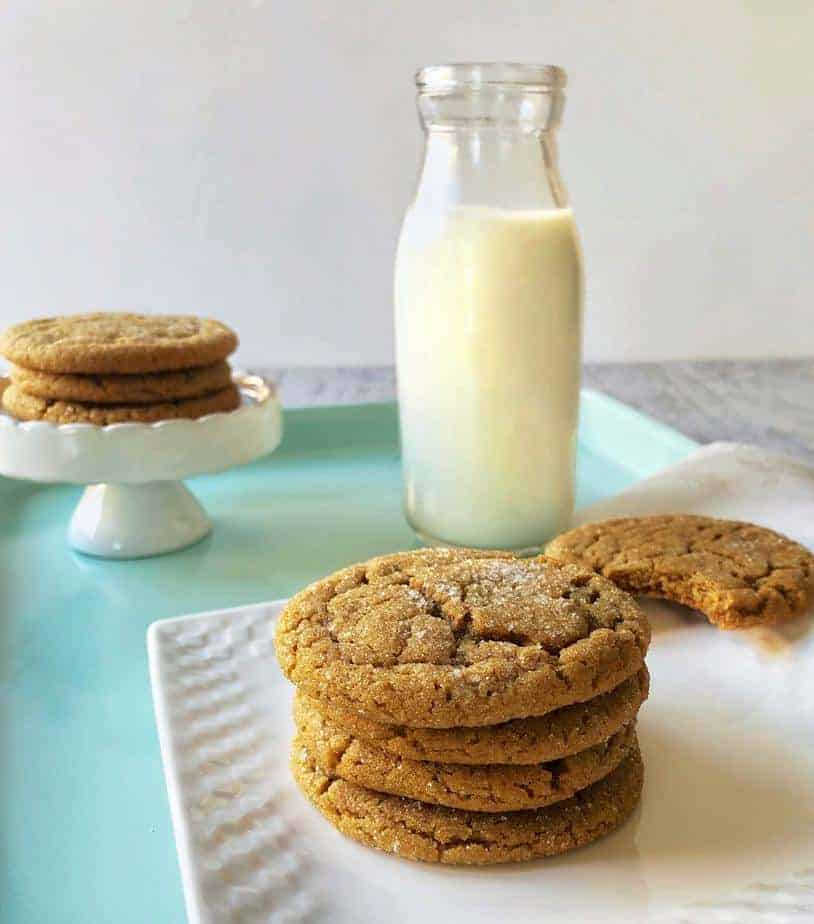 ginger snaps or ginger gringles in a stack with bottle of milk.