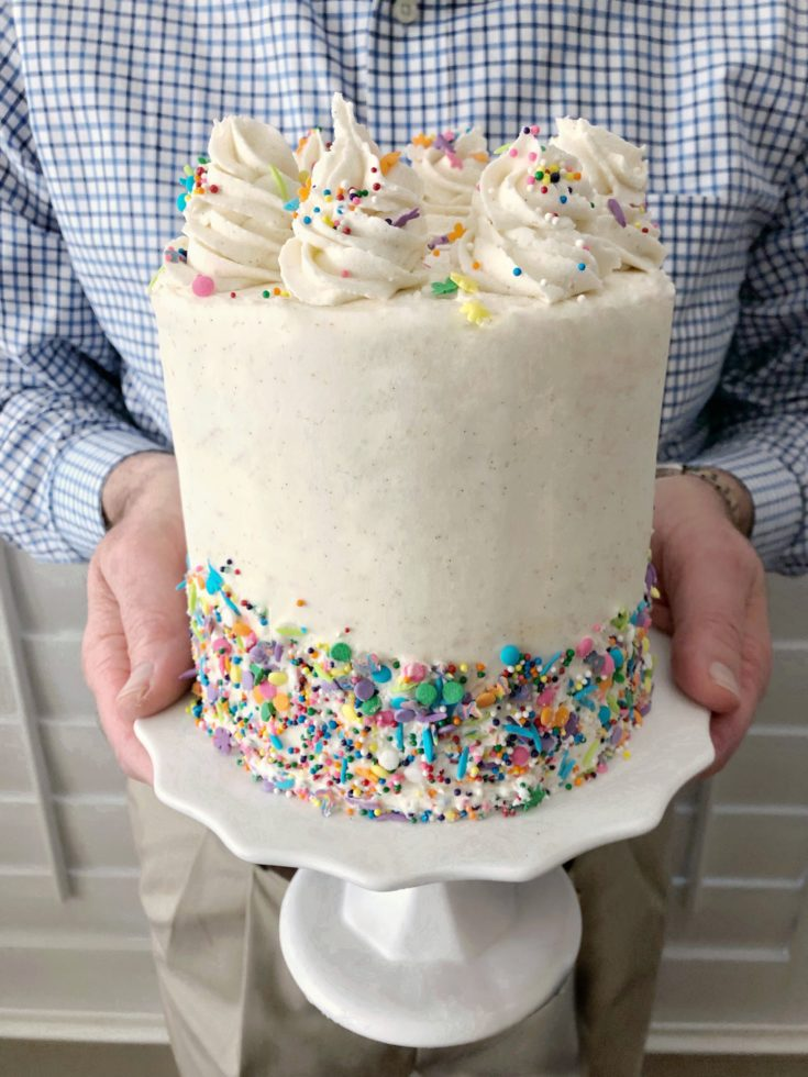 White easy classic vanilla layer cake with sprinkles on a white cake stand