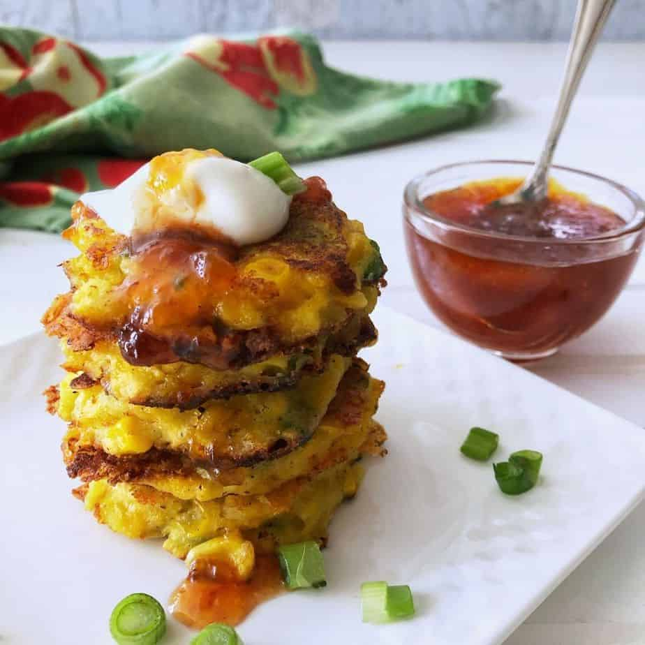 stack of corn fritters with bowl of chili peach sauce. featured image