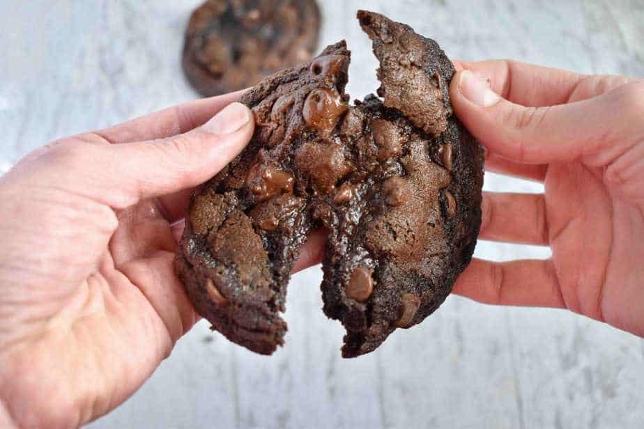 hands breaking double chocolate cookie in half