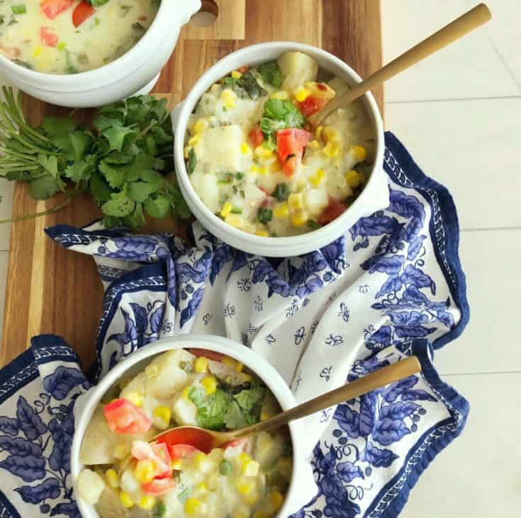 3 bowls of coconut corn chowder on a blue and white napkin and cutting board