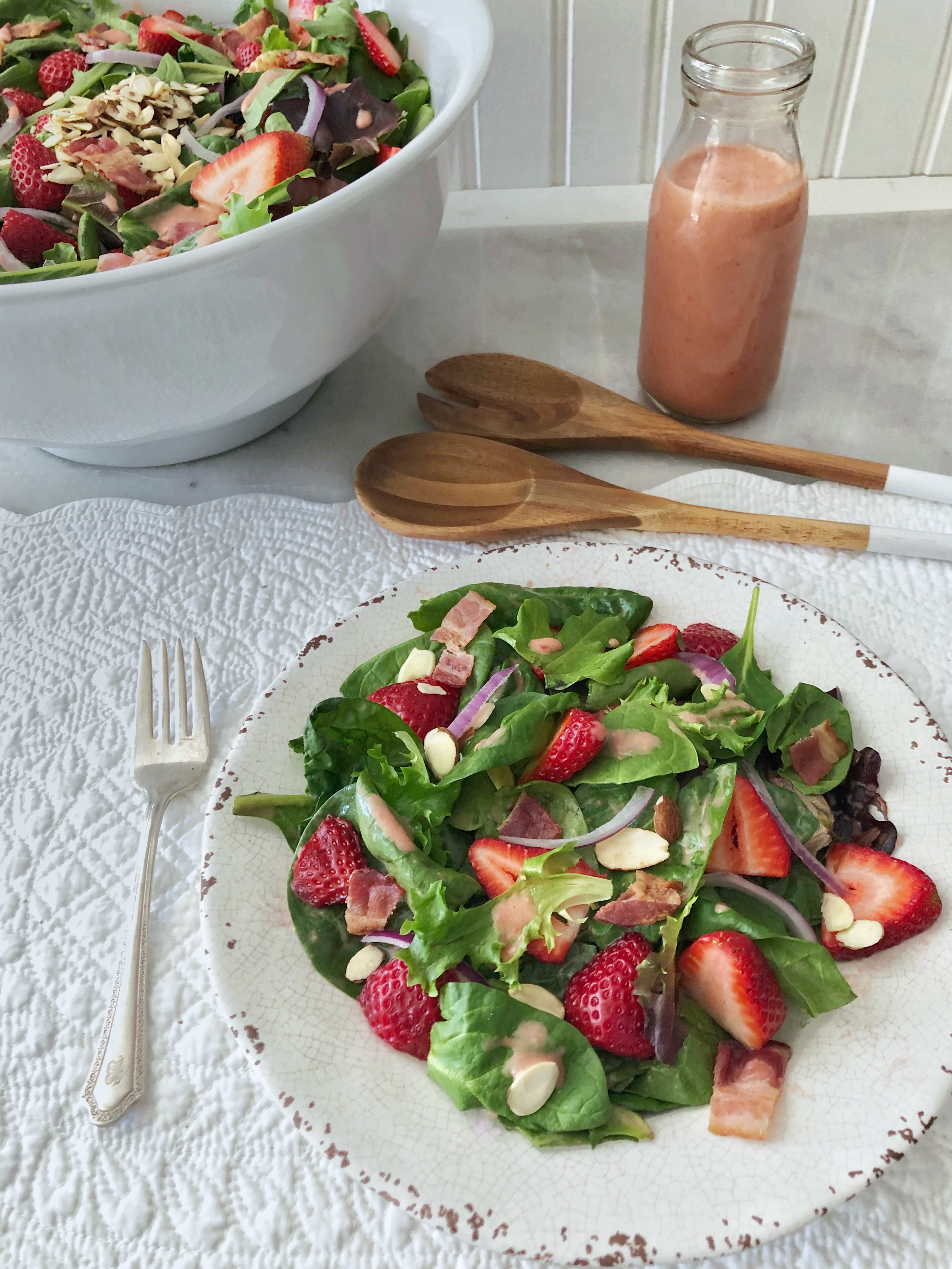 a small plate of green salad with fresh strawberries, spinach, bacon, toasted almonds and red onion.