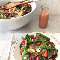 fresh green salad with spinach, strawberries, bacon, toasted almonds and red onion.