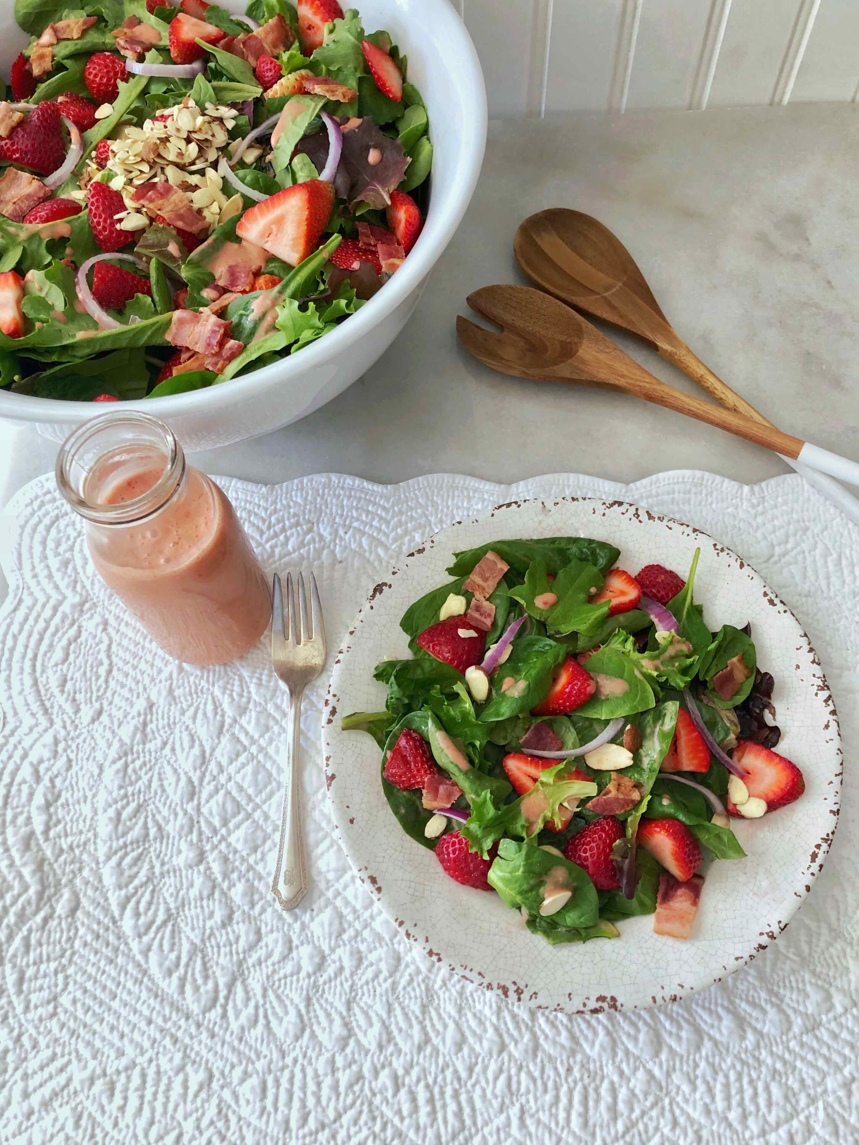 strawberry spinach salad serving with bottle of strawberry vinaigrette