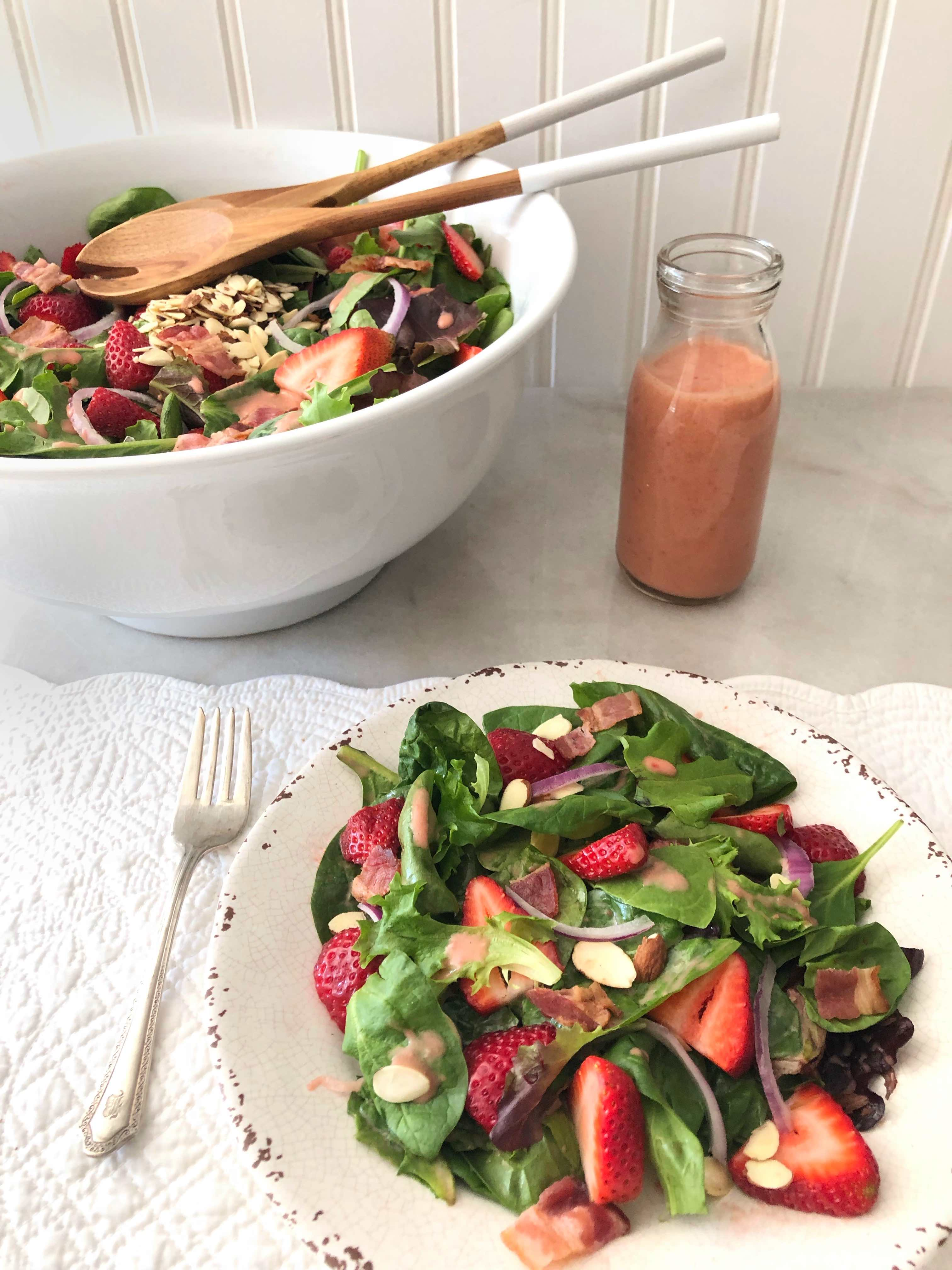 salad tongs sitting in bowl full of strawberry spinach salad with single plate in foreground.