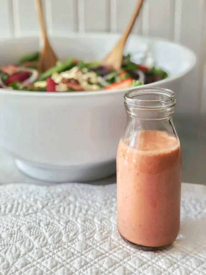 white bowl with salad servers and bottle of strawberry vinaigrette
