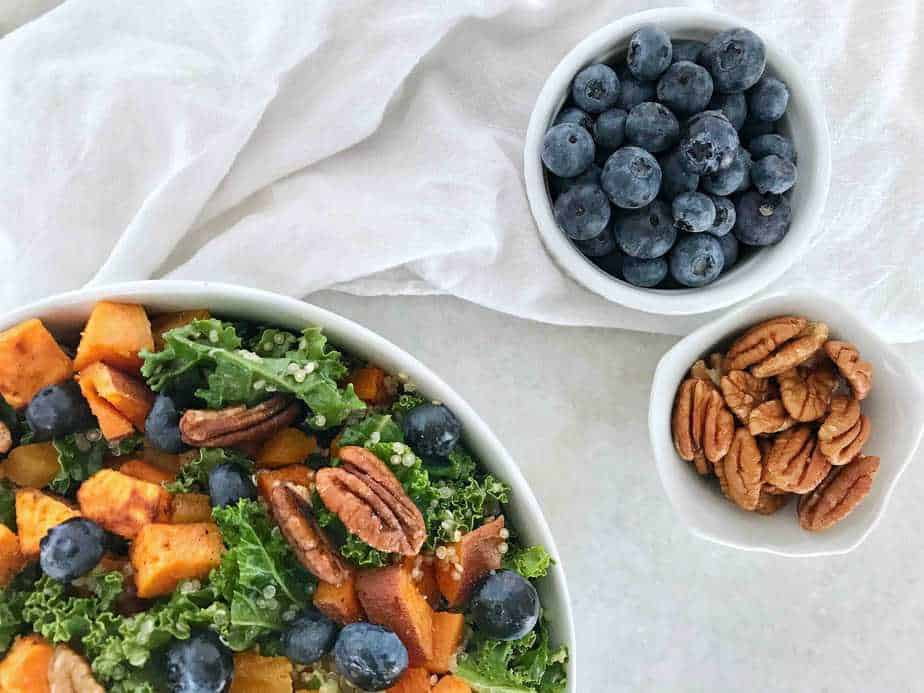 salad with bowls of blueberries and pecan on side